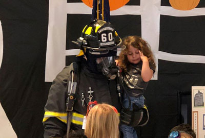Dressed as a volunteer firefighter, Watchung Borough Board of Education member Tom Sicola participates in a school assembly with his daughter.