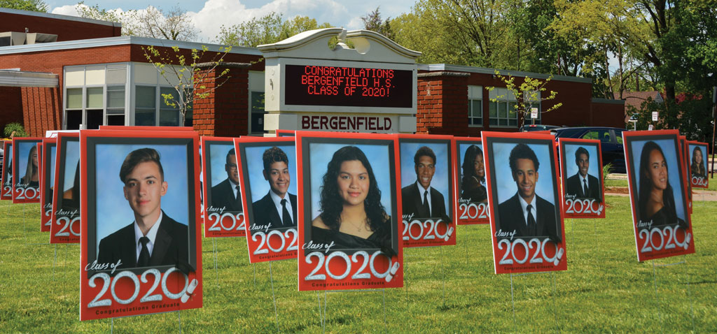 "Bergenfield: Celebrating with Lawn Signs Bergenfield High School celebrated its 292 graduating seniors with photographs of the students on the front lawn of the school. ""We didn't know what to expect as far as the public reaction to the signs,"" says Chris Langschultz, special assistant to the superintendent at Bergenfield, ""but we knew that we wanted to acknowledge our seniors. It seems like every time I drive by the school, I see parents there taking a photo of their child next to their sign, or tying balloons to their student's sign, or a student taking pictures of their friend's photos."""