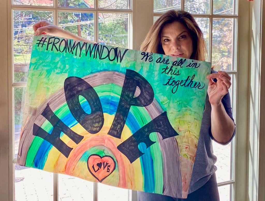 Words of Encouragement in Linden Linden High School Principal Yelena Horre holding a poster she hung in her front window. It was part of a program in which families were encouraged to post rainbows or other uplifting messages in their front windows and doors.